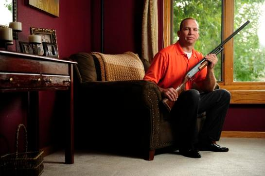 James Hagerman poses with a .12 gauge shotgun in his Fort Collins home on Wednesday, September 26, 2012. AAron Ontiveroz, The Denver Post