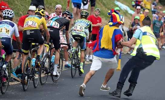 A French Gendarme restrains a fan during stage 19 of the 2015 Tour de France from Saint-Jean-de-Maurienne to La Troussuire on July 24, 2015 in La Toussuire, France.